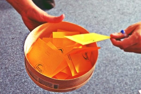 Puszka z kartkami do głosowania. Widoczna ręka jednej osoby, która ja trzyma. Druga osoba (eidoczna ręka) wkłada kartkę.